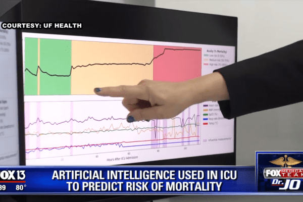 """Video still of a hand pointing at a screen with graphs on it. News headline reads """"Artificial Intelligence used in ICU to predict risk of mortality"""""""