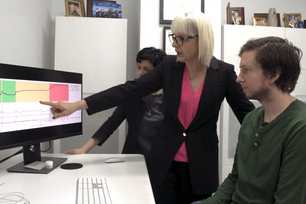 Researchers pointing at a screen with a color-coded graph on it
