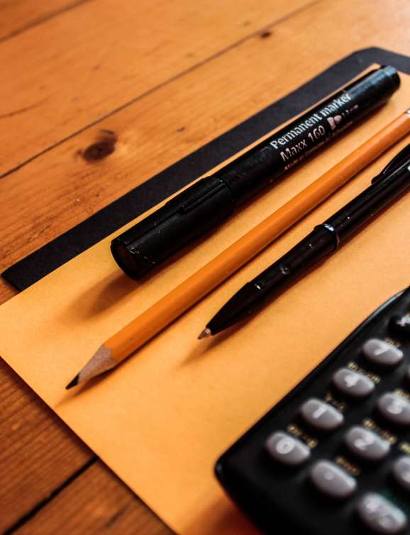 Image of calculator, pens, and pencils