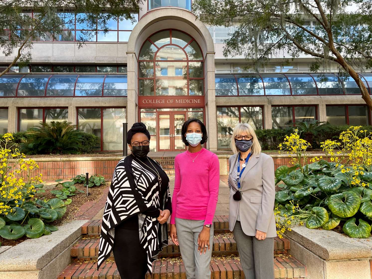Photo of Drs. Della V. Mosley, Crystal Johnson-Mann, and Azra Bihorac standing in front of a UF College of Medicine building